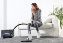 Kobieta z alergią odkurza w salonie